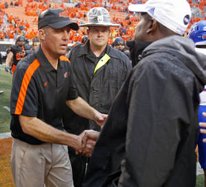 Photo - Oklahoma State head coach Mike Gundy and Kansas head coach Turner Gill shake hands following a college football game where the Oklahoma State University Cowboys (OSU) defeated the University of Kansas Jayhawks (KU) 70-28 at Boone Pickens Stadium in Stillwater, Okla., Saturday, Oct. 8, 2011 Photo by Steve Sisney, The Oklahoman