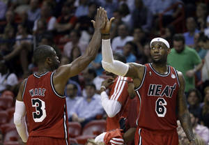 photo - Miami Heat's LeBron James (6) high-fives teammate Dwyane Wade (3) as they head to the bench for a timeout during the second half of an NBA basketball game against the Portland Trail Blazers in Miami, Tuesday, Feb. 12, 2013. James became the first player in NBA history to score 30 points and shoot at least 60 percent in six straight games as the Heat defeated the Trail Blazers 117-104. (AP Photo/Alan Diaz)