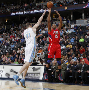 Photo - Atlanta Hawks forward Al Horford, right, takes a shot over Denver Nuggets center Kosta Koufos in the first quarter of an NBA basketball game in Denver on Monday, March 4, 2013. (AP Photo/David Zalubowski)