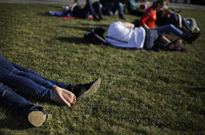 Photo - A couple at left, lie on the lawn under the Olympic cauldron at the 2014 Winter Olympics, Wednesday, Feb. 12, 2014, in Sochi, Russia. Temperatures are predicted near 60 degrees Fahrenheit in Sochi on Wednesday. (AP Photo/David Goldman)