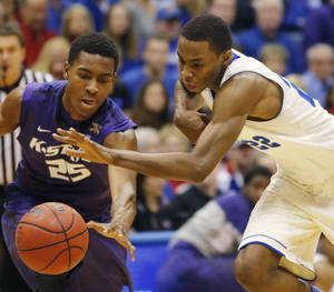 Photo - Kansas guard Andrew Wiggins, right, gets to the ball ahead of Kansas State's Wesley Iwundu (25) during the first half of an NCAA college basketball game in Lawrence, Kan., Saturday, Jan. 11, 2014. (AP Photo/Orlin Wagner)