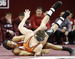 Photo - OU's Kendric Maple, left, wrestles Zach Neibert of Virginia Tech in the 141-pound class during the Beauty and the Beast event at the Lloyd Noble Center in Norman, Okla., where the University of Oklahoma wrestling team competed against Virginia Tech and the OU women's gymnastics team competed against North Carolina State, Friday, Jan. 27, 2012. Photo by Nate Billings, The Oklahoman