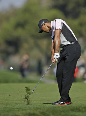 Photo - Tiger Woods hits to the second green on the south course at Torrey Pines during the first round of the Farmers Insurance Open golf tournament  Thursday, Jan. 23, 2014, in San Diego. (AP Photo/Lenny Ignelzi)