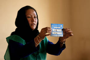 Photo - An Independent Election Commission (IEC) employee shows a ballot to observers at a polling station in Kabul, Afghanistan, Saturday, June 14, 2014. Despite a Taliban threat to stay away, Afghans lined up Saturday to vote in a presidential runoff between two candidates who both promise to improve ties with the West and combat corruption as they confront a powerful Taliban insurgency and preside over the withdrawal of most foreign troops by the end of the year. (AP Photo/Massoud Hossaini)