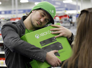 Photo - FILE - In this  Friday, Nov. 22, 2013,  file photo, Emanuel Jumatate, from Chicago, hugs his new Xbox One after he purchased it at a Best Buy in Evanston, Ill. Microsoft is billing the Xbox One, which includes an updated Kinect motion sensor, as an all-in-one entertainment system rather than just a gaming console. (AP Photo/Nam Y. Huh)