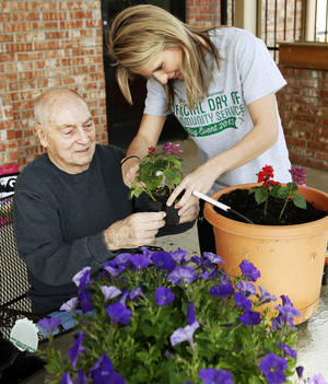 Photo - Ronald Clayton and University of Oklahoma student Mindi Coleman plant flowers Saturday at the Daily Living Center, 3000 N Rockwell, in Bethany.  Photo by Nate Billings, The Oklahoman