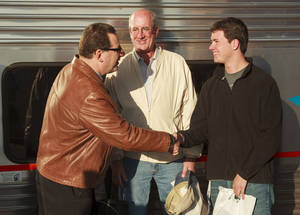 Photo - Amtrak Media Relations Manager Marc Magliari, left, congratulates Rooke Jackson as the Heartland Flyer's millionth passenger as he gets ready to board the Heartland Flyer in Oklahoma City with his father, Wayne J. Jackson, on Nov. 15, 2013. <strong>Provided - Provided</strong>