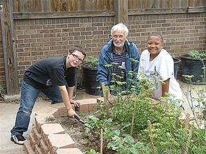 Photo - Student Alex Lynch, left, volunteer gardener Richard Carothers and student Isaiah Marshall harvest vegetables as part of a Del City Elementary School gardening project. Photo provided by Midwest City-Del City Public Schools