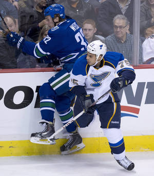 Photo - Vancouver Canucks right wing Dale Weise (32) is put into the boards by St. Louis Blues right wing Ryan Reaves (75) during the second period of an NHL hockey game Friday, Jan. 10, 2014, in Vancouver, British Columbia. (AP Photo/The Canadian Press, Jonathan Hayward)