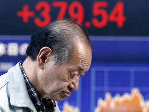 Photo - A man walks by an electronic stock board of a securities firm in Tokyo, Thursday, June 27, 2013.  Stock markets from Sydney to Shanghai extended gains for a second day Thursday after the U.S. said quarterly growth may be weaker than expected, raising investors' hopes that the Federal Reserve would delay plans to wind down its stimulus program.(AP Photo/Koji Sasahara)