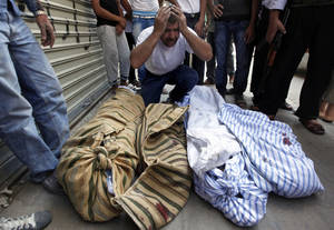 Photo -   A Syrian man grieves over the bodies of four members of his family, who were killed when an airstrike hit their house, as they lie on the side of the street outside a field hospital in Aleppo, Syria, Friday, Aug. 17, 2012. Rebel footholds in Aleppo have been the target of weeks of Syrian shelling and air attacks as part of wider offensives by President Bashar Assad's regime. Rebels have been driven from some areas, but the report of clashes near the airport suggests the battles could be shifting to new fronts.(AP Photo/ Khalil Hamra)