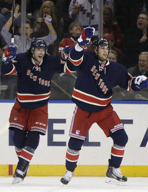 Photo - New York Rangers left wing Benoit Pouliot, left, celebrates with center Derick Brassard (16) after getting the assist on Brassard's first-period goal against the Chicago Blackhawks in an NHL hockey game at Madison Square Garden in New York, Thursday, Feb. 27, 2014. (AP Photo/Kathy Willens)