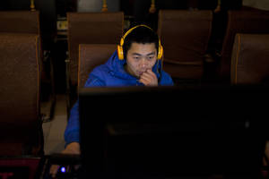 photo - A man uses a computer at an internet cafe in central Beijing, China, Friday, Dec. 28, 2012. China's new communist leaders are increasing already tight controls on Internet use and electronic publishing following a spate of embarrassing online reports about official abuses. (AP Photo/Alexander F. Yuan)