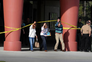 Photo - Patrons leave Cobb theater after a shooting Monday, Jan. 13, 2014, in Wesley Chapel, Fla. Authorities say a retired Tampa police officer has been charged with fatally shooting a man during an argument over cellphone use at the theater. (AP Photo/The Tampa Tribune, Cliff Mcbride)