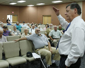 Photo - U.S. Rep. Tom Cole, right, R-Oklahoma, speaks during a town hall meeting in Duncan, Okla, Wednesday, Aug. 28, 2013. (AP Photo/Sue Ogrocki) ORG XMIT: OKSO103