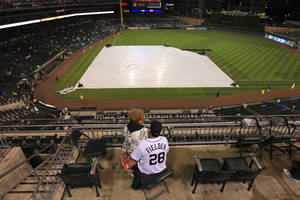 Photo -   Jim and Debbie Michalski sit through a rain delay before a baseball game between the Minnesota Twins and the Detroit Tigers at Comerica Park in Detroit, Friday, Sept. 21, 2012. (AP Photo/Carlos Osorio)