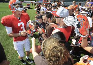 Photo - Cleveland Browns quarterback Brandon Weeden signs autographs for fans after NFL football training camp on Sunday, July 29, 2012, in Berea, Ohio. (AP Photo/Tony Dejak) ORG XMIT: OHTD110