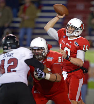 Photo - Ball State quarterback Keith Wenning (10) throws as pass as offensive lineman Steven Bell (66) blocks Arkansas State defensive end Chris Stone (42) in the first quarter of the GoDaddy Bowl NCAA college football game, Sunday, Jan. 5, 2014, in Mobile, Ala. (AP Photo/G.M. Andrews)