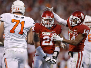 photo - BEDLAM FOOTBALL / CELEBRATION: Oklahoma&#039;s Tom Wort (21) celebrates with Aaron Colvin (14) beside Oklahoma State&#039;s Parker Graham (71) during the Bedlam college football game between the University of Oklahoma Sooners (OU) and the Oklahoma State University Cowboys (OSU) at Gaylord Family-Oklahoma Memorial Stadium in Norman, Okla., Saturday, Nov. 24, 2012. Oklahoma won 51-48. Photo by Bryan Terry, The Oklahoman