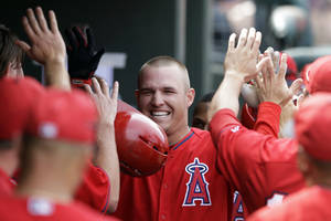 Photo - Los Angeles Angels' Mike Trout is congratulated by teammates after hitting a two-run home run during the sixth inning of a spring exhibition baseball game against the Kansas City Royals, Thursday, March 20, 2014, in Surprise, Ariz. (AP Photo/Darron Cummings)