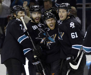 Photo - San Jose Sharks' Joe Pavelski (8) celebrates his goal with teammates Brad Stuart (7), Brent Burns (88) and Justin Braun (61) during the first period of an NHL hockey game against the Detroit Red Wings on Thursday, Jan. 9, 2014, in San Jose, Calif. (AP Photo/Marcio Jose Sanchez)