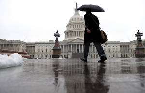 Photo - A person walks on Capitol Hill in Washington, Monday, Dec. 9, 2013, as rain, snow, sleet and freezing rain affected most of the U.S. Mid-Atlantic region on Sunday and into Monday. (AP Photo/Susan Walsh)