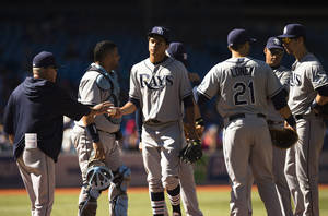 Photo - Tampa Bay Rays' Chris Archer, center, is taken out of the game by manager Joe Maddon, left, during the third inning of a baseball game against the Toronto Blue Jays in Toronto, Saturday, Sept. 28, 2013. (AP Photo/The Canadian Press, Mark Blinch)