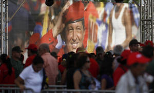 Photo - A large image of Venezuela's late President Hugo Chavez is on display where mourners line up to view his body lying in state at the military academy in Caracas, Thursday, March 7, 2013. While Venezuela remains deeply divided over the country's future, the multitudes weeping and crossing themselves as they reached the president's coffin early Thursday were united in grief and admiration for a man many considered a father figure. (AP Photo/Ariana Cubillos)