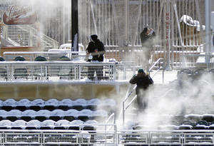 Photo - Mainelle Moore, right, hoses down snow-covered seats in the right field at Target Field with hot water prior to the start of the first game of a day/night baseball double header against the Miami Marlins Tuesday, April 23, 2013 in Minneapolis, Minn. Monday's game was postponed due to snow. (AP Photo/Jim Mone)