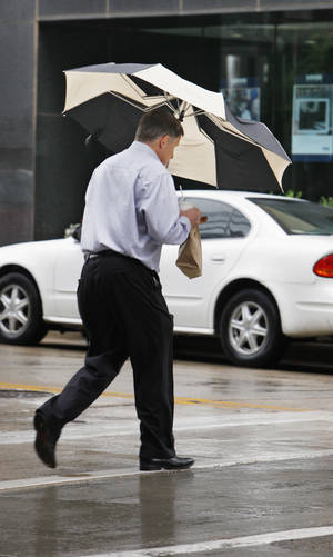 Photo - A pedestrian hurries across the intersection of Park and Robinson avenues as rain falls during the lunch hour in downtown Oklahoma City on Monday.  Photo by Paul B. Southerland, The Oklahoman <strong>PAUL B. SOUTHERLAND</strong>