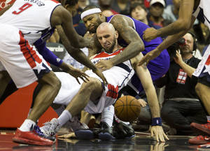 Photo - Sacramento Kings center DeMarcus Cousins grabs Washington Wizards center Marcin Gortat as during a scramble for a loose ball during the second half of an NBA basketball game, Sunday, Feb. 9, 2014, in Washington. The Wizards defeated the Kings 93-84. (AP Photo/ Evan Vucci)