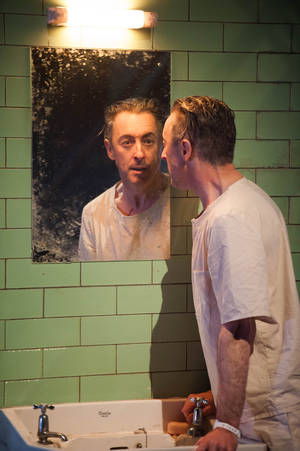"Photo - This undated theater image released by National Theatre of Scotland shows Alan Cumming in ""Macbeth.""  In the play, Cumming appears as a patient in a white-tiled mental hospital for whom the plot of ""Macbeth is sort of a schizophrenic nightmare. Producers said Friday that the Tony Award winning Scottish actor will bring his one-man ""Macbeth to Broadway's Ethel Barrymore Theatre beginning April 7. It will run through June 30. (AP Photo/National Theatre of Scotland, Manuel Harlan)"