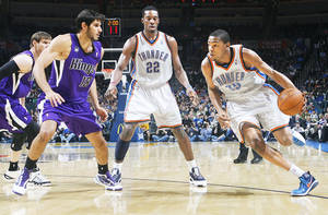 photo - Oklahoma City's Kevin Durant, right, drives the ball past the Kings' Omri Casspi during Wednesday's game at the Ford Center. Photo by Chris Landsberger, The Oklahoman