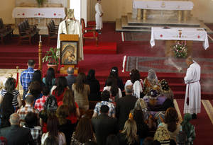 Photo - Iraqi Christians pray during Easter mass at Mar Youssif Chaldean Church in Baghdad, Iraq, Sunday, March 31, 2013. The Chaldean Church is an Eastern Rite church affiliated with the Roman Catholic Church. (AP Photo/ Karim Kadim)