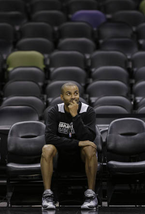 Photo - San Antonio Spurs' Tony Parker, of France, sits on the sidelines NBA basketball practice Wednesday, June 12, 2013, in San Antonio.  The Spurs lead the Miami Heat 2-1 in the best-of-seven series, Game 4 of the NBA finals series is scheduled for Thursday.  (AP Photo/Eric Gay)