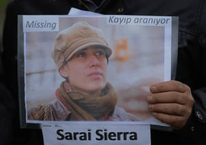 Photo - A member of the Istanbul-based Association For Families With Lost Relatives hands out flyers with photos of Sarai Sierra, a New York City woman who disappeared while on vacation in Istanbul, urging anyone with information to call police, in Istanbul, Turkey, Thursday, Jan. 31, 2013. Sierra, a 33 year-old mother of two, has been missing since Jan. 21, when she was due to return home. Turkish police have set up a special unit to search for her and are trying to trace a man she had been in contact with during her stay.(AP Photo)