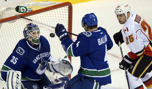 photo - From left, Vancouver Canucks goalie Cory Schneider, Keith Ballard and Calgary Flames' Steve Begin watch the puck after Schneider made a save during the second period of their NHL hockey game, Wednesday, Jan. 23, 2013, in Vancouver, British Columbia. (AP Photo/The Canadian Press, Darryl Dyck)