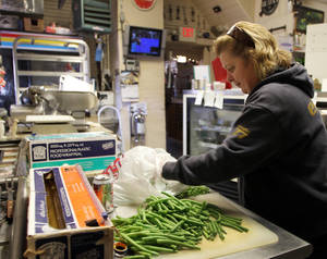 Photo - In this photo taken Thursday Dec. 6, 2012, owner of Robie's Country Store and Deli Debbie Chouinard works on cutting up green beans.  (AP Photo/Jim Cole)