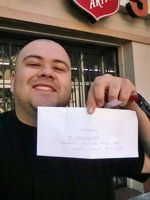 Photo - This image provided by Sergio Loza shows Loza holding up an envelope that had cash hidden in it in San Francisco, on Sunday, May 25, 2014. Loza followed the clues from a Twitter user using the handle @HiddenCash to find the money. The mysterious person has been hiding money throughout the city since Friday that's leading scores on a scavenger hunt.  (AP Photo/Sergio Loza)