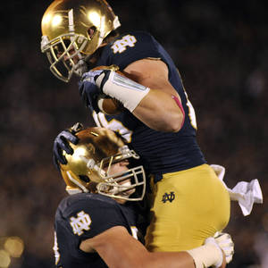 Photo - Notre Dame tight end Troy Niklas, right, celebrates with teammate Nick Martin after a Niklas' catch resulted in a touchdown pass during the first quarter of a college football game Saturday, Oct. 19, 2013, in South Bend, Ind. (AP Photo/Joe Raymond)