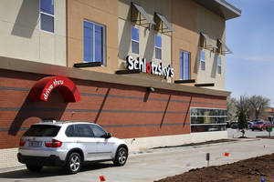 Photo - A car visit the drive-thru at Midwest City's new Schlotzsky's, which is unique for the upscale apartments above it. <strong>Jim Beckel - THE OKLAHOMAN</strong>