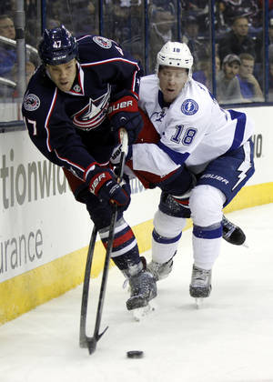 Photo - Columbus Blue Jackets' Dalton Prout, left, works for the puck against Tampa Bay Lightning's Ondrej Palat, of the Czech Republic, in the first period of an NHL hockey game in Columbus, Ohio, Tuesday, Dec. 3, 2013. (AP Photo/Paul Vernon)