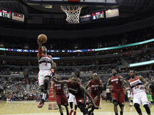 Photo - Washington Wizards guard John Wall (2) drives to the basket past Miami Heat center Chris Bosh (1) in the second half of an NBA basketball game on Wednesday, Jan. 15, 2014, in Washington. Wall had 25 points and the Wizards won 114-97. (AP Photo/Alex Brandon)