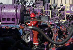 Photo -   A worker adjusting hoses during a hydraulic fracturing operation at an Encana Corp. gas well, near Mead, Colo. AP File Photo  <strong>Brennan Linsley -  AP </strong>