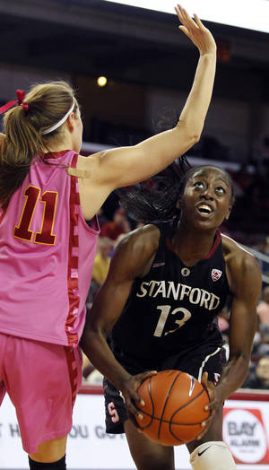 Photo - Stanford forward Chiney Ogwumike, right, eyes the basket against Southern California forward Cassie Harberts (11) during the second half of an NCAA college basketball game Friday, Feb. 21, 2014, in Los Angeles. Stanford won 64-59. (AP Photo/Alex Gallardo)