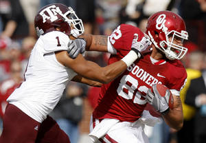 Photo - Oklahoma's Roy Finch (22) fights off Texas A&M's Trent Hunter (1) during the college football game between the Texas A&M Aggies and the University of Oklahoma Sooners (OU) at Gaylord Family-Oklahoma Memorial Stadium on Saturday, Nov. 5, 2011, in Norman, Okla. Oklahoma won 41-25.  Photo by Bryan Terry, The Oklahoman