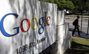 Photo -                    A man walks past a Google sign at the company's headquarters in Mountain View, Calif. Google has announced that it is buying Skybox Imaging.                                        AP Photo