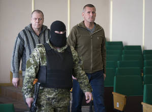 Photo - John Christensen, right, a senior Sgt. in the Danish army and his colleague, both members of a group of foreign military observers are escorted by a pro-Russian militant to attend a press conference in the city hall of Slovyansk, eastern Ukraine, Sunday, April 27, 2014. As Western governments vowed to impose more sanctions against Russia and its supporters in eastern Ukraine, a group of foreign military observers remained in captivity Saturday accused of being NATO spies by a pro-Russian insurgency. The German-led, eight-member team was traveling under the auspices of the Organization of Security and Cooperation in Europe when they were detained Friday. (AP Photo/Alexander Zemlianichenko)