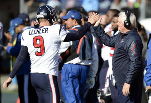 Photo - Houston Texans interim head coach Wade Phillips, right, congratulates punter Shane Lechler (9) after a kick against the Tennessee Titans in the second quarter of an NFL football game Sunday, Dec. 29, 2013, in Nashville, Tenn. (AP Photo/Mark Zaleski)