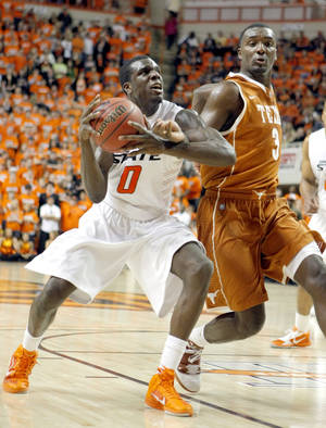 Photo - Oklahoma State's Jean-Paul Olukemi (0) tries to get past Texas' Jordan Hamilton (3) during the basketball game between Oklahoma State and Texas, Wednesday, Jan. 26, 2011, at Gallagher-Iba Arena in Stillwater, Okla. Photo by Sarah Phipps, The Oklahoman ORG XMIT: KOD